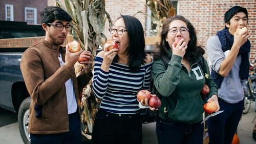 four students standing next to each other eating apples