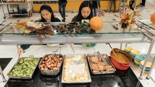two female students getting food from a buffet