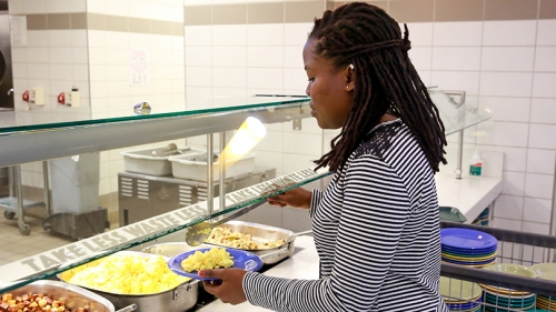 a student filling her plate with scrambled eggs in 53 Commons dining hall