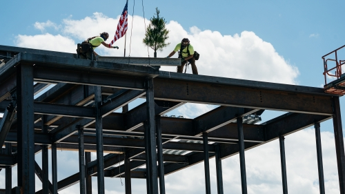 Workers install the highest steel beam atop the new Center for Engineering and Computer Science.