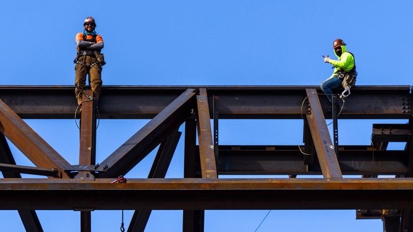 Construction workers await the beam's arrival.