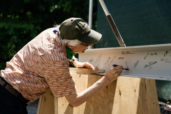Eric Hansen, an associate professor of engineering at Thayer, signs the beam before it is set into place.